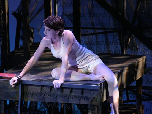 A woman wearing white sitting on a wooden platform and looking off stage