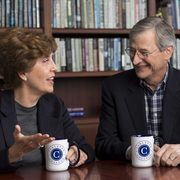 Cathy Paglia and Wally Weitz pose with Carleton coffee mugs
