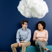 Two smiling students sit on a couch beneath a cotton cloud