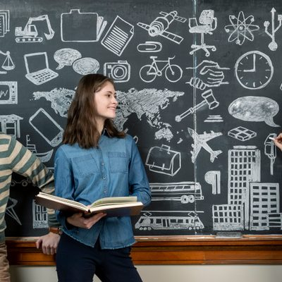 Three students stand in front of an elaborately-illustrated chalkboard