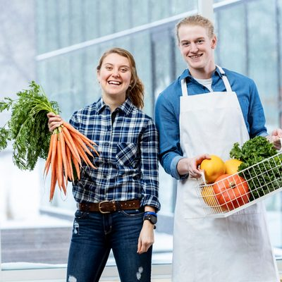 Two students smile and pose with an assortment of fresh vegetables