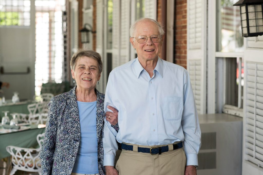 An elderly couple pose arm-in-arm, smiling