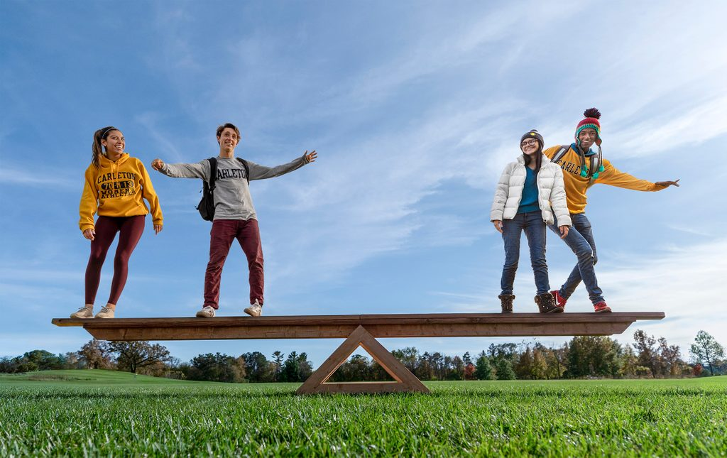 Four students balance on a gigantic see-saw