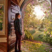 Photo illustration: A student look out a doorway containing a magical landscape with butterflies and topiary