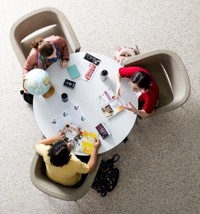 Three students seated at a round table, viewed from overhead