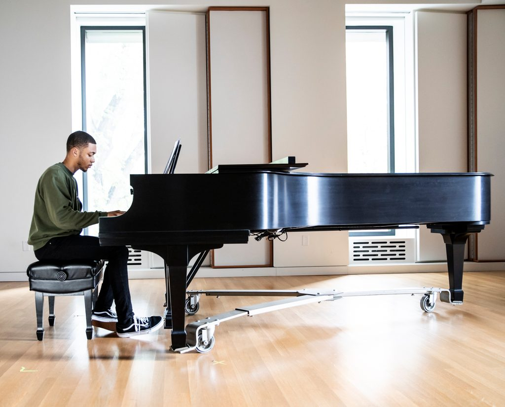 a student plays a grand piano in a light-filled room