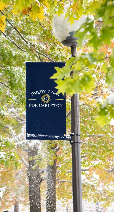 "snow falls upon a banner reading ""Every Carl for Carleton"""
