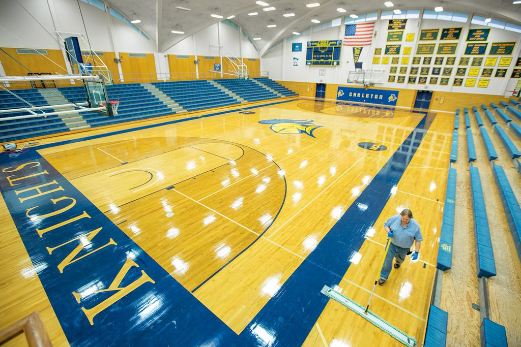 a man sweeps a basketball court