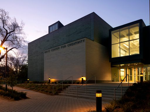The main entrance of the Weitz Center, at night, with lights in the windows.